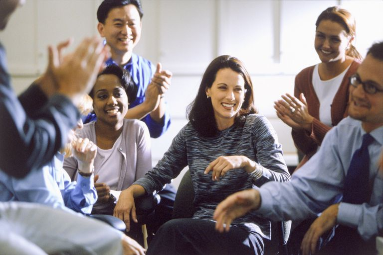 Business people applauding in a meeting about the progress of their change management efforts.