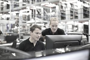 Man and woman looking at computer in logistics warehouse