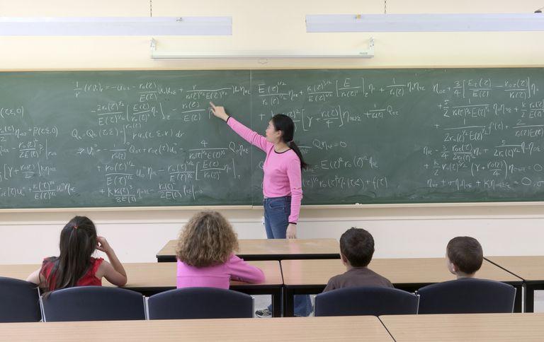 math student explaining equation at chalk board