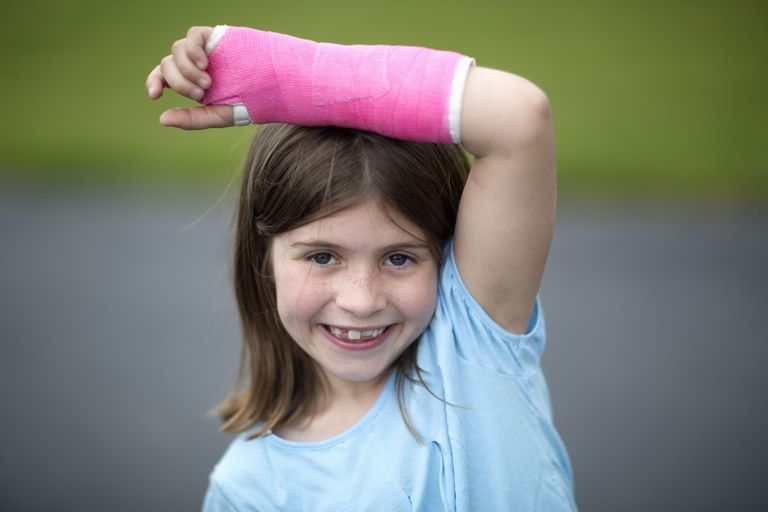 a young girl with a pink cast on her arm