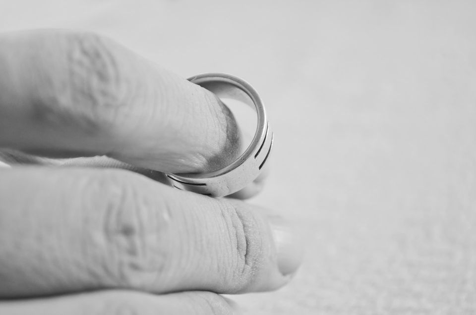 A wedding ring slipping off of a finger