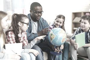 a teacher holding a globe and teaching students