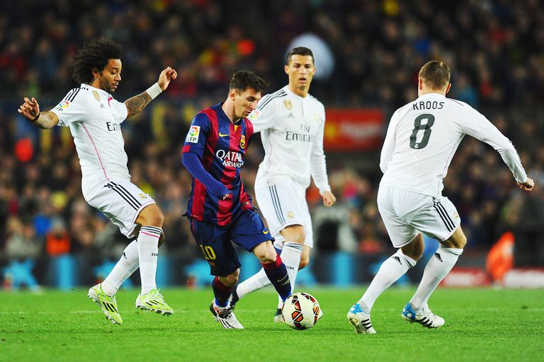 Lionel Messi of Barcelona takes on Marcelo (L), Cristiano Ronaldo (2R) and Toni Kroos of Real Madrid