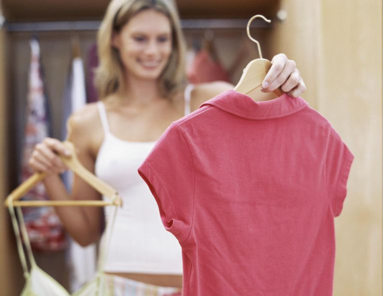 Young woman holding clothes on a hanger