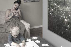 Toddler putting together a white jigsaw puzzle