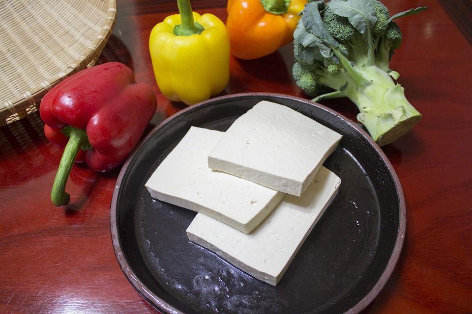 tofu in pan next to vegetables