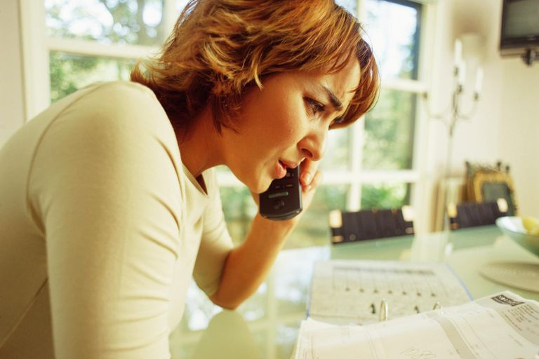 Woman worried over debt and talking on phone