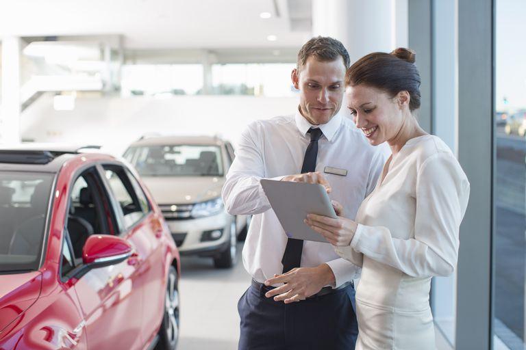 Salesman and female customer using digital tablet in car dealership