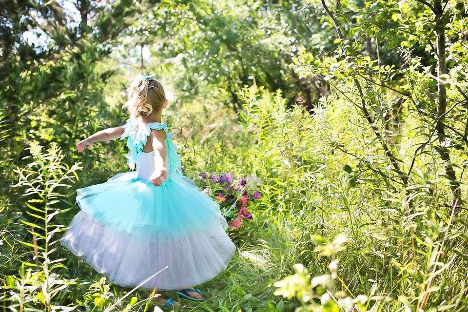 Girl dressed as fairy, dancing in garden.