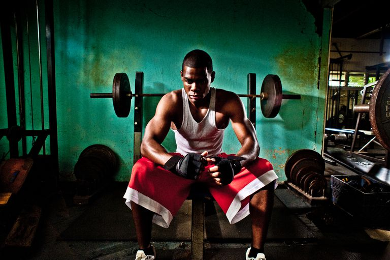 A male athlete relaxes between sets at an old gym in San Diego, CA