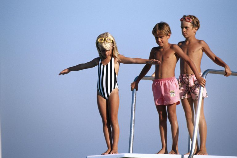 Children (6-9) standing on diving board, low angle view
