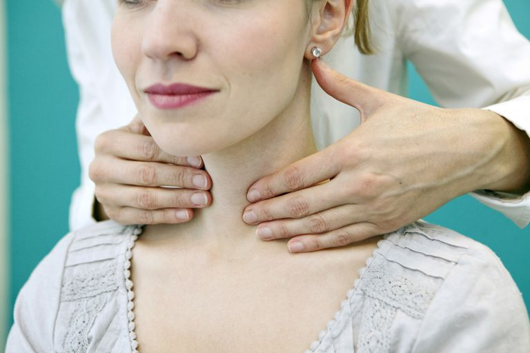 Woman having her thyroid examined