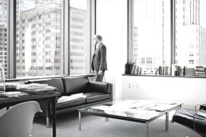 Businessman standing looking out window in office