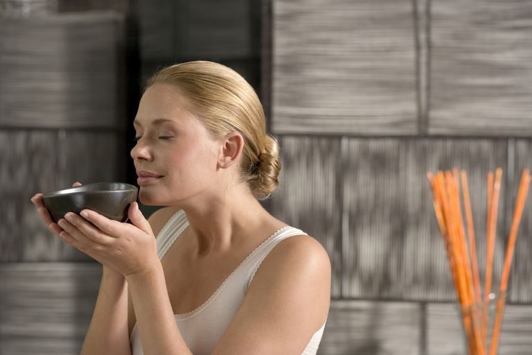 Germany, young woman holding tea bowl, eyes closed, close-up