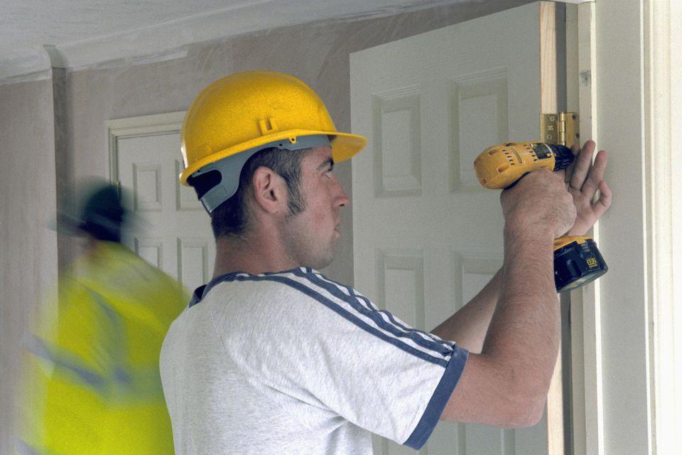 Interior door hanging using cordless drill.