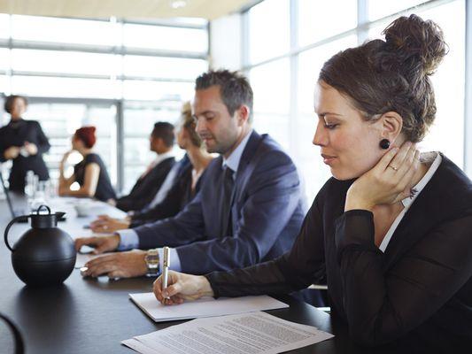 Businesswoman taking notes at meeting