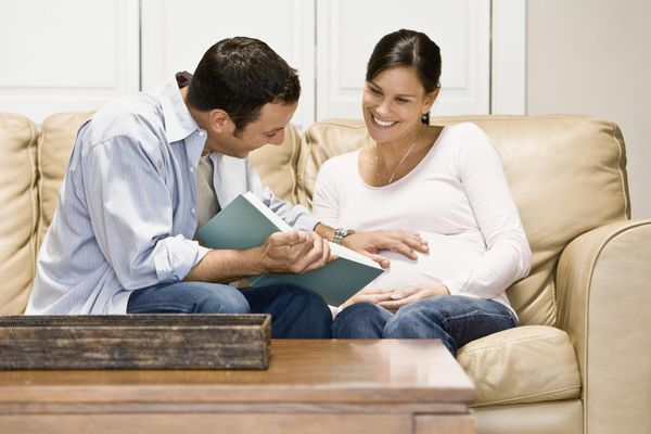Man reading beside pregnant wife.