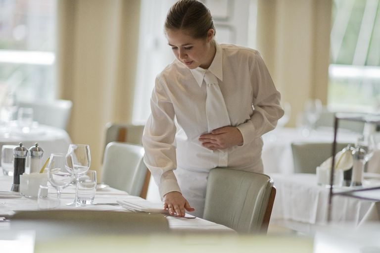 Waitress repositions flatware on restaurant table