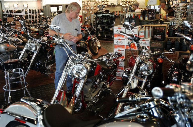 man checking out used motorcycles
