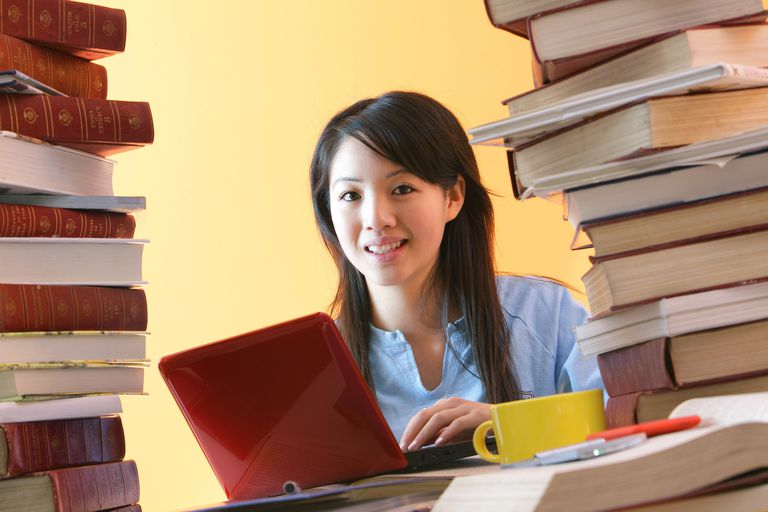 Woman on laptop surrounded by books