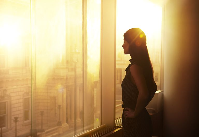 Business woman looking over the city at sunrise.