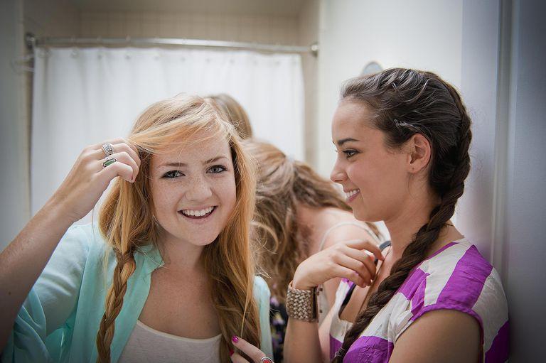 Teen girls doing each others' hair in bathroom
