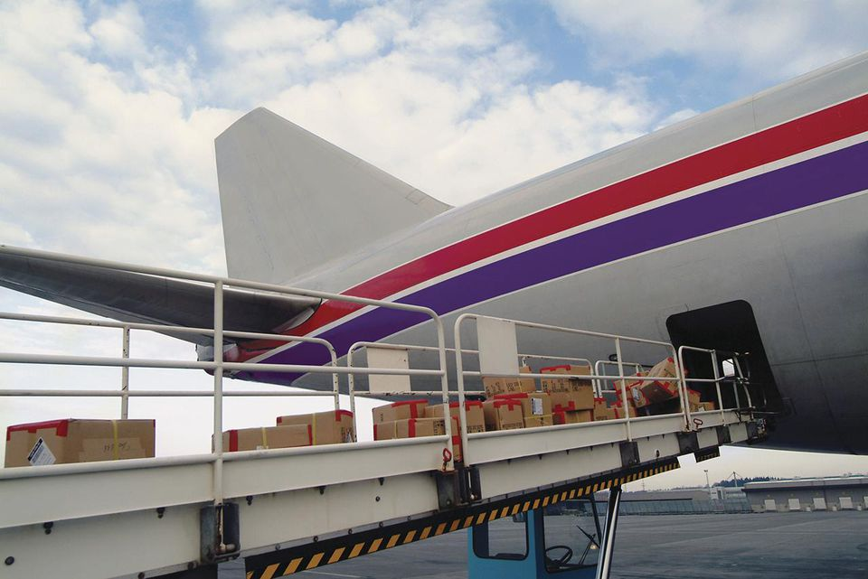 Cardboard Containers on a Conveyor Belt Being Loaded into the Rear of a Cargo Plane