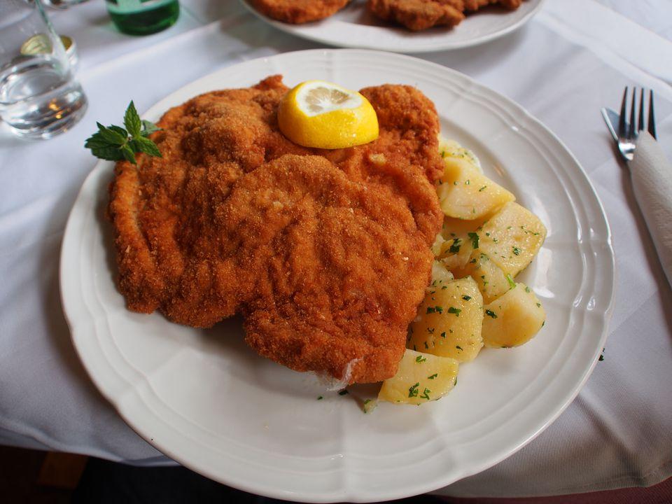 Wiener Schnitzel served with lemon, parsley and potatoes in Vienna, Austria