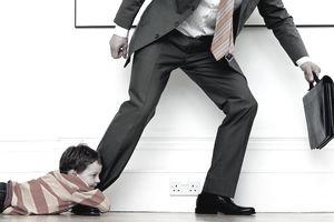Boy holding onto businessman's leg