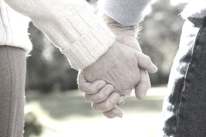 Older couple holding hands.