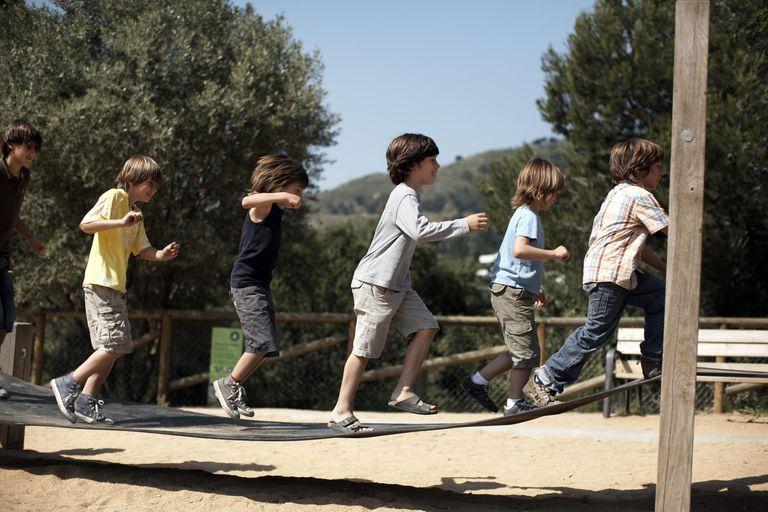 Boys jump on playground structure.