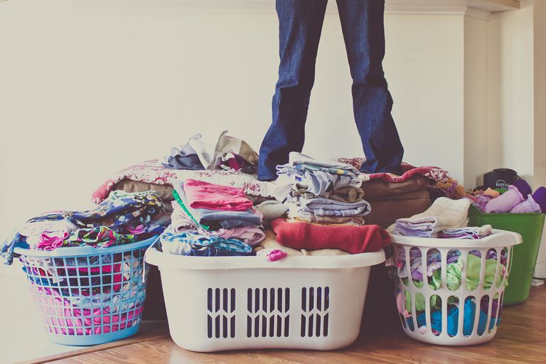 Woman standing on laundry pile
