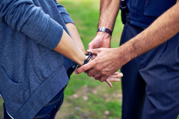 Police officer putting handcuffs on criminal