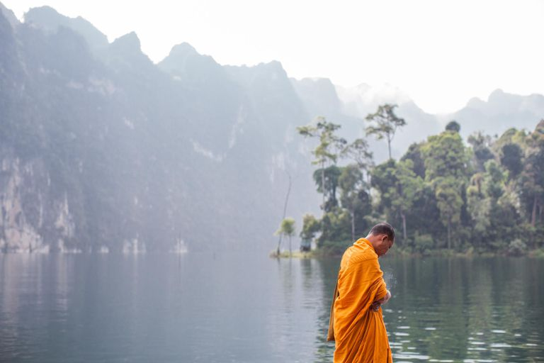 A buddhist monk smokes by Chieow Laan lake