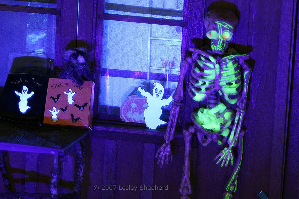 Photo of miniature porch scene lit with a skeleton lit by miniature black lights.