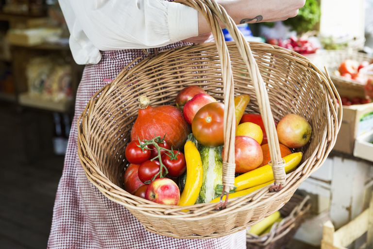 Woman holding basket with vegetables in farm shop