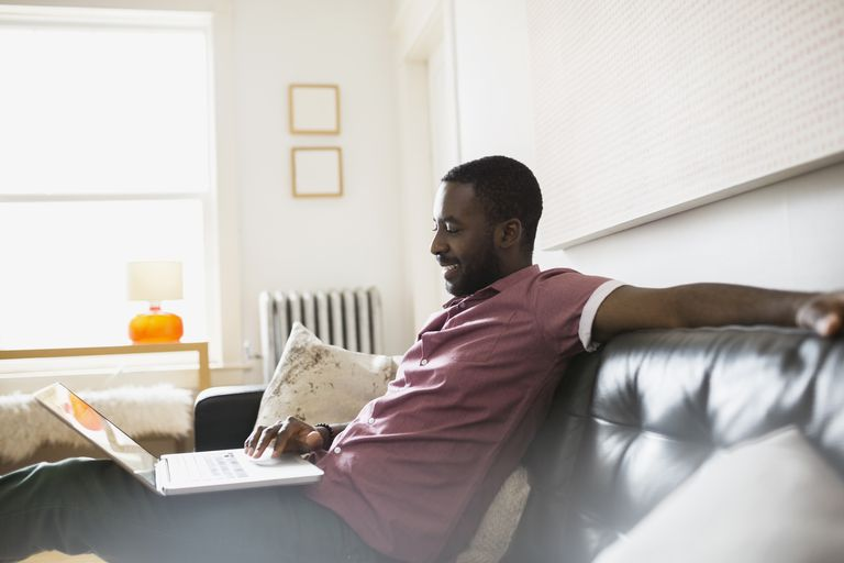 Man relaxing using laptop on living room sofa