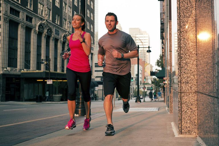 A healthy couple runs before sundown in the streets of the city.