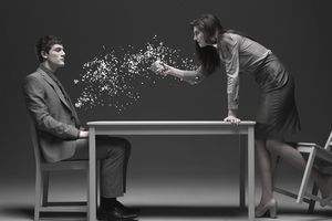Businesswoman throwing paper pieces on man, side view (digital composite)