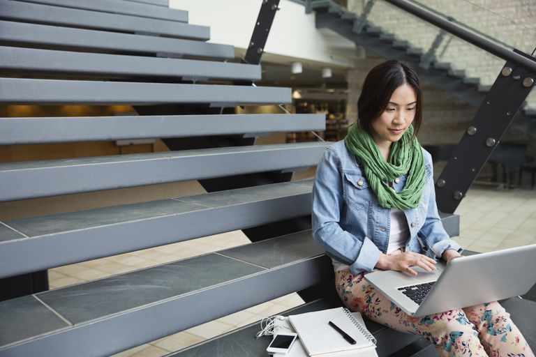 Female student sitting on bleachers with laptop