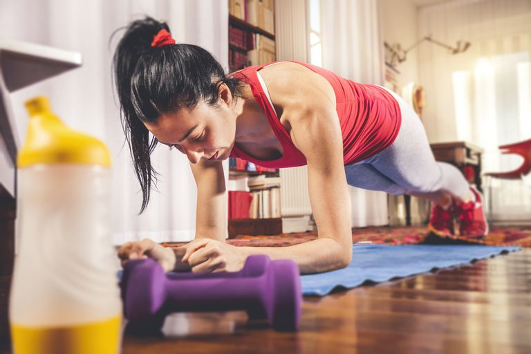 One woman exercising at home following instructions on laptop