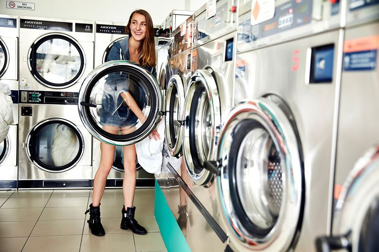 Girl loading washing machine in laundromat