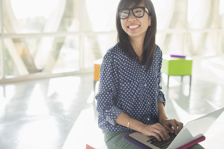Happy casual businesswoman using laptop in sunny office