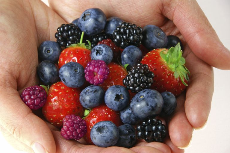 photo of many different berries held in a woman's hands