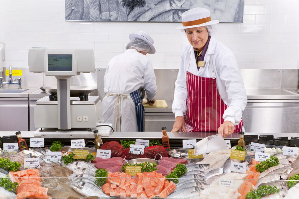 Staff At Fresh Fish Counter In Supermarket