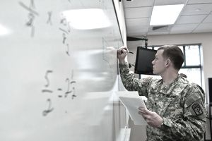 Spc. Dustin Salmon, a computer detection systems repairer with the 542nd Support Maintenance Company, 593rd Sustainment Brigade, solves a problem from a worksheet of high school-level math questions Feb. 12 during a month-long Basic Skills Education Program class held by the 593rd every other month at the Stone Education Center on Joint Base Lewis-McChord, Wash. The class, started one year ago by the brigade, is intended to raise Soldiers' General Technical scores and improve their math, vocabulary and reading comprehension skills.