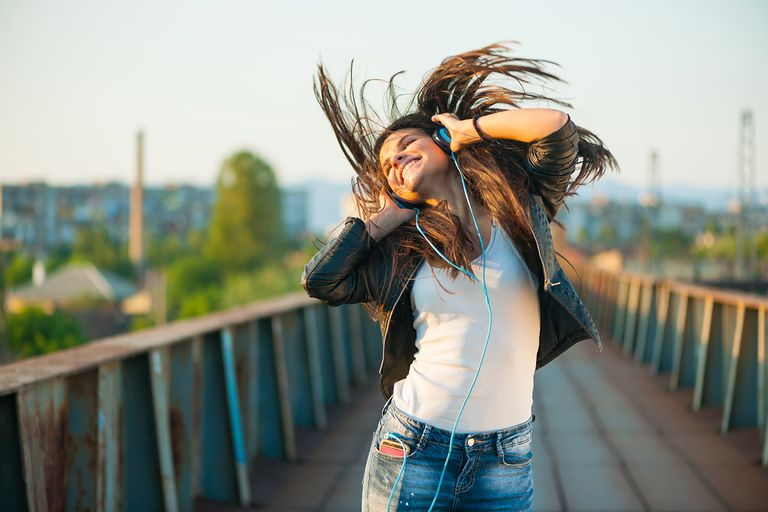Woman dancing while listening to music in headphones.