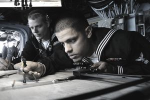 Navy quartermaster checks navigation chart aboard USS Essex. SASEBO, Japan (April 14, 2011) Quartermaster 3rd Class Elvis Gomez, right, checks a navigation chart while Quartermaster 2nd Class Kevin Bell makes a log entry on the bridge of the forward-deployed amphibious assault ship USS Essex (LHD 2). Essex is returning to Sasebo after completing a three-month patrol of the western Pacific Ocean.