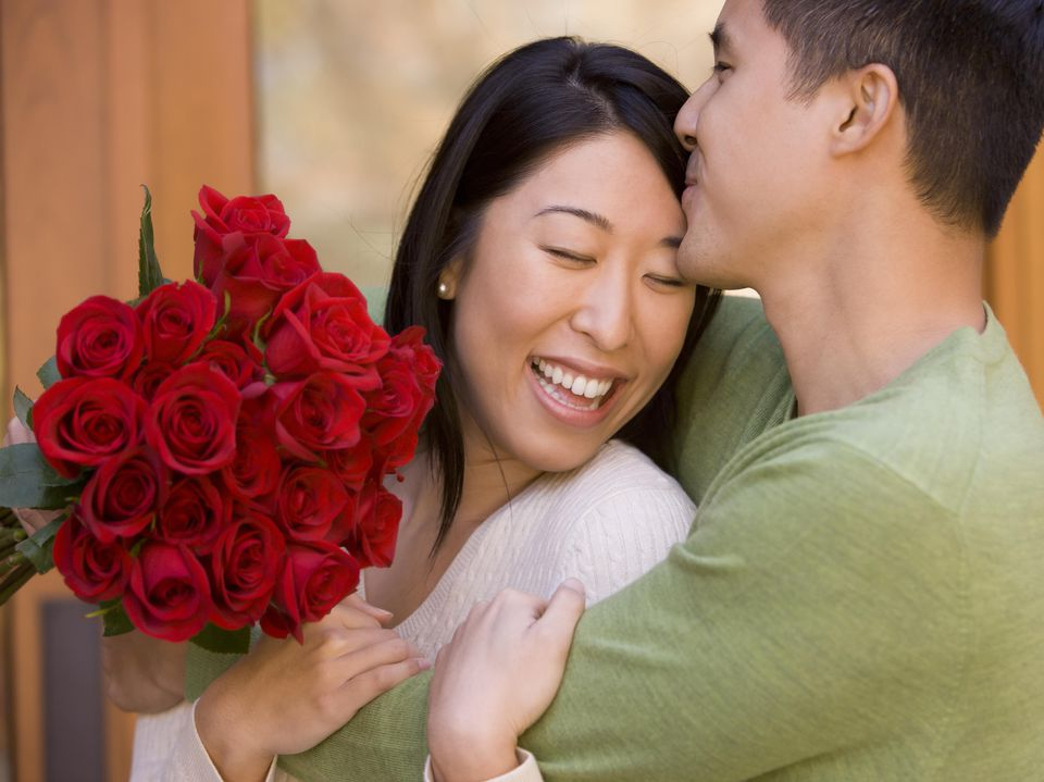 Young Couple Hugging and Kissing with Roses