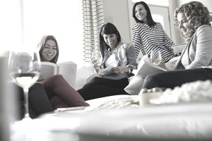 Happy female friends with wineglasses reading books at house party